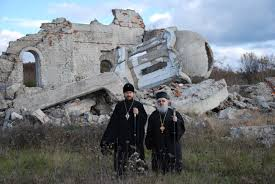 Kosovo Priests standing before destroyed church