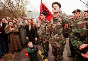 in yonkers at the parking lot of the regal hotel hundreds of albanian KLA volunteers prepared to go to albania as family members cried Drita Hasangjerat,wipes away a tear, holding her son ben, at left if Tair Bajramaj and far left is Pasko Gjokaj wipes away tear 2 brothers(names coming) in military uniforms younger one crying as their father prepares to go to war