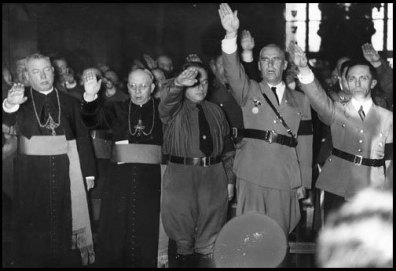 Catholic clergy and Nazi officials, including Joseph Goebbels (far right) and Wilhelm Frick (second from right), give the Nazi salute. Germany, date uncertain.